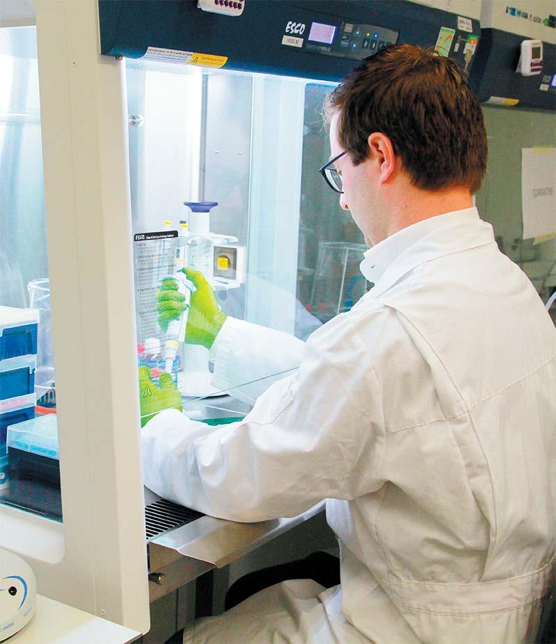 Kasper Spoelstra aan het werk in een door Salm en Kipp geleverde bioveiligheidskast van Esco